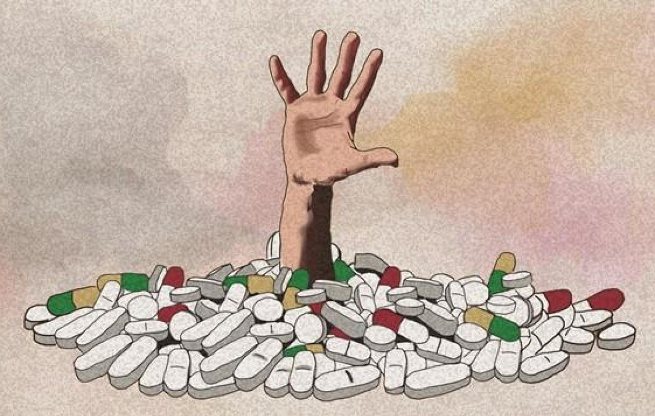 Hand reaching out of opioid pills