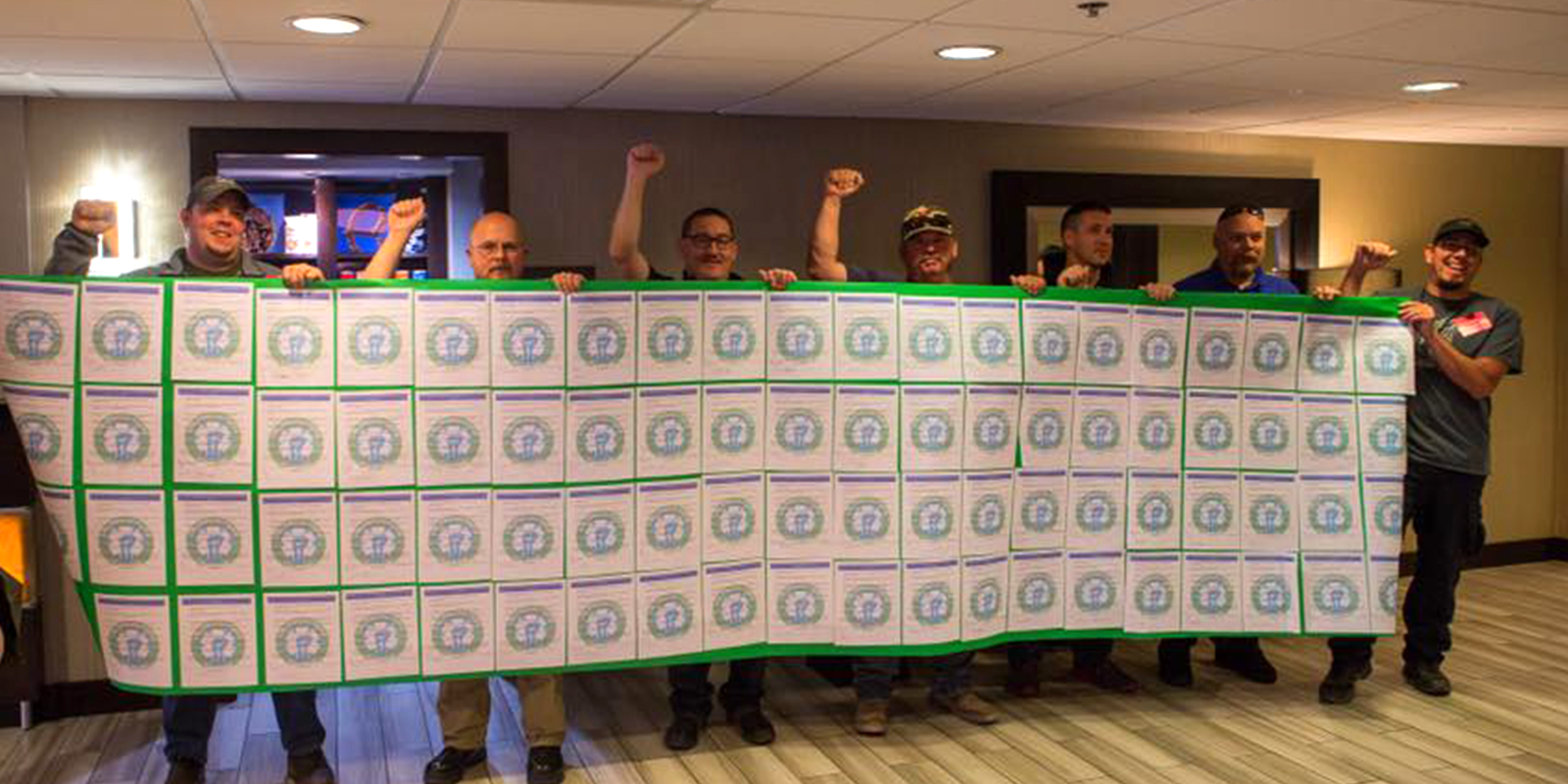 EMS Local 2960 members hold up copies of a petition joined together to form a large banner
